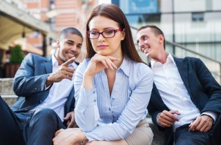 two business men whisper behind business woman