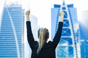Business woman with arms raised in victory