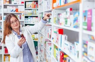 Female pharmacist reaching for medication