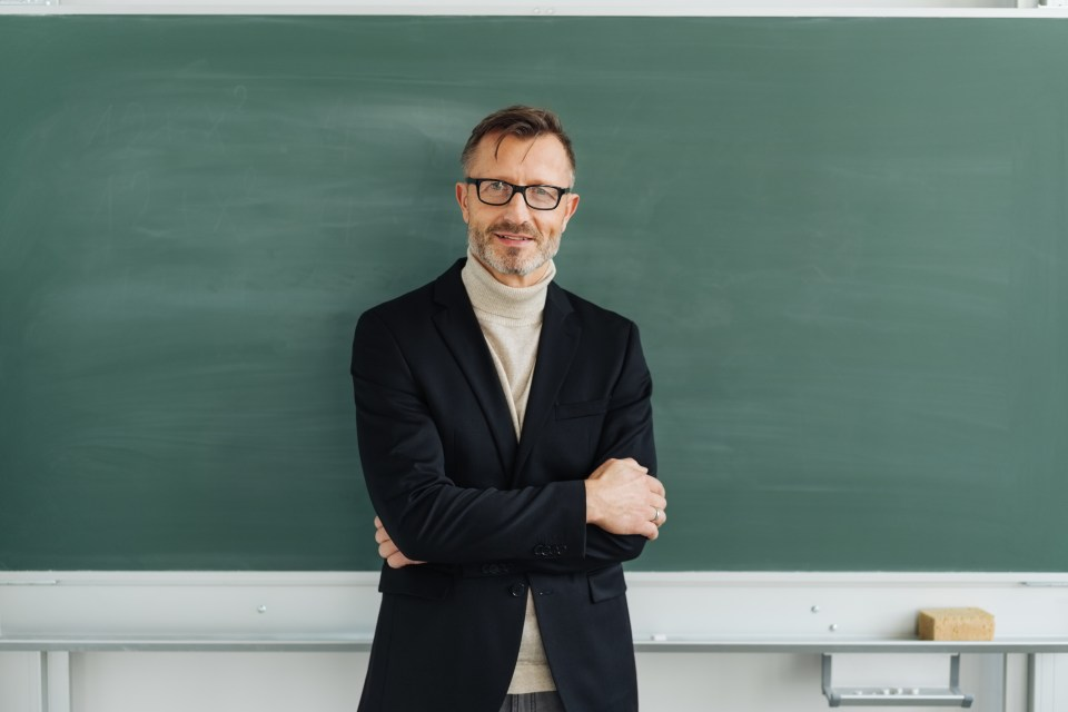Well dressed man wearing glasses stands in front of chalkboard