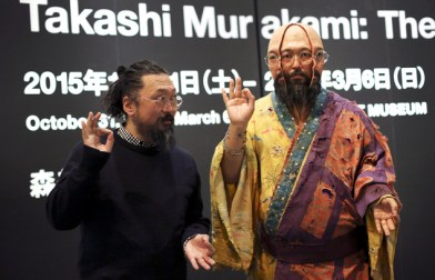 "In this Dec. 29, 2015 photo, Japanese artist Takashi Murakami poses with one of his works exhibited at ""The 500 Arhats"" exhibition at Mori Art Museum in Tokyo. In the gentrified kitsch landscape Murakami depicts, 500 grotesque priests parade along dazzlingly colorful giant panels. (AP Photo/Eugene Hoshiko)"