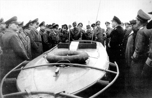 Military and political officials are introduced to the Linsen explosive motor boat. Among the assembled audience are Luftwaffe General Adolf Galland and Armaments Minister Albert Speer.