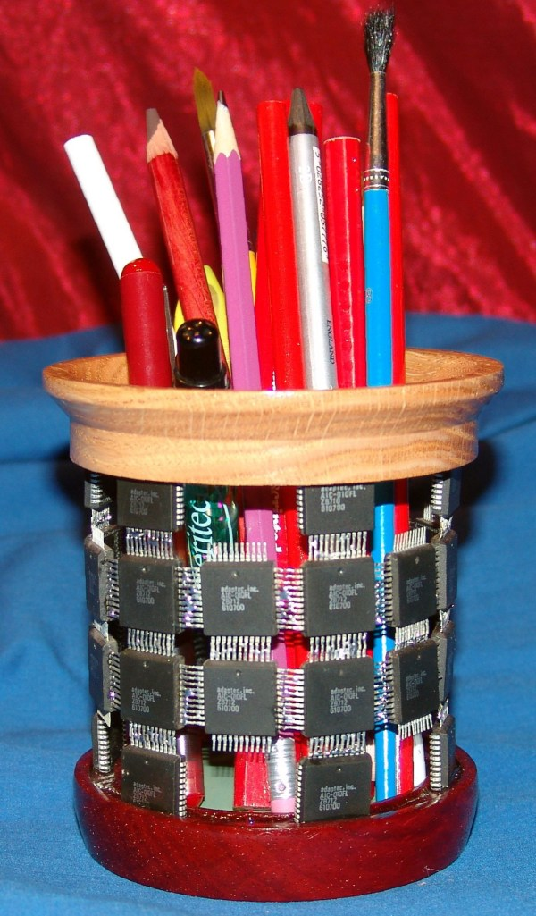 """Dennis Montville, """"Pencil Holder"""" 66-18 - This is intended to hold pencils and pens and markers. It has a piece of thin vinyl on the bottom to protect pen tips from damage. It is made using integrated circuit chips to form the body with wood at the top and bottom. I have several more examples available in the gallery. wood, electronic components, 5 x 4, $45"""