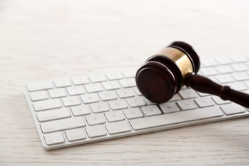 Gavel with computer keyboard on wooden table closeup