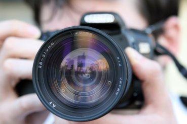 A person holding a digital camera up close