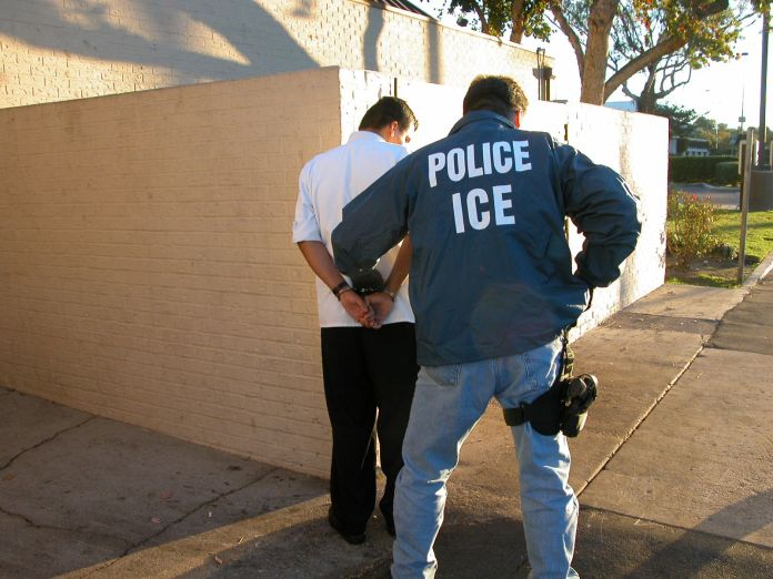 An Immigration and Custom Enforcement Officer arresting a man in a white shirt