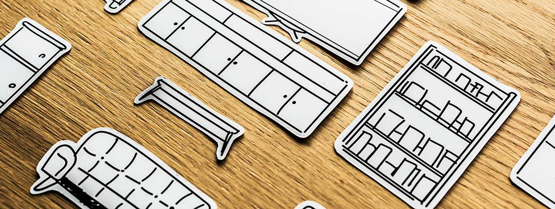 Paper cut outs of furniture and personal effect laid out on a wooden desk to show property to be distributed before probate.