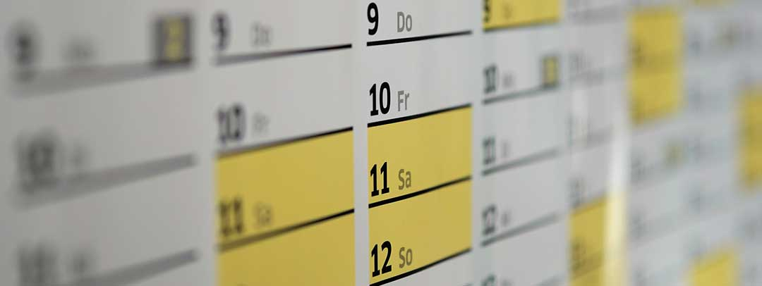 A close up shot of a yellow, white and black calendar to indicate the length of time the process takes.