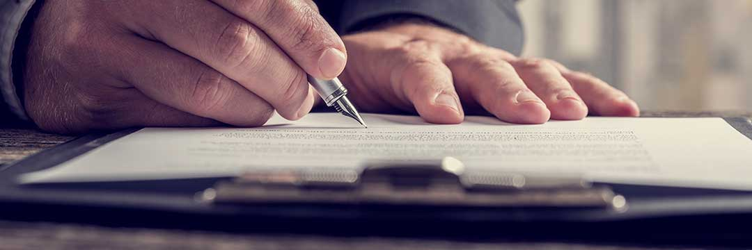 A man writing his judicial affadavit, with a close up shot of the pen and his hands.