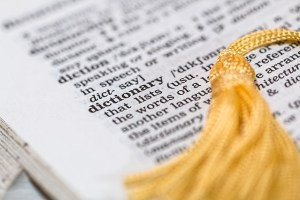 "Dictionary open to page with definition of ""dictionary,"" with gold tassel."