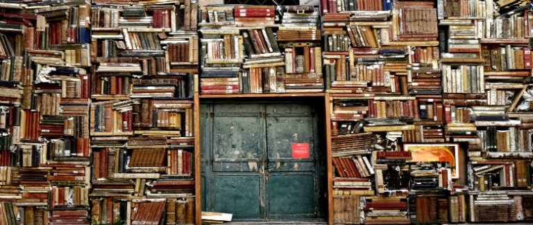 Stacks of books forming a wall in which there is a green door