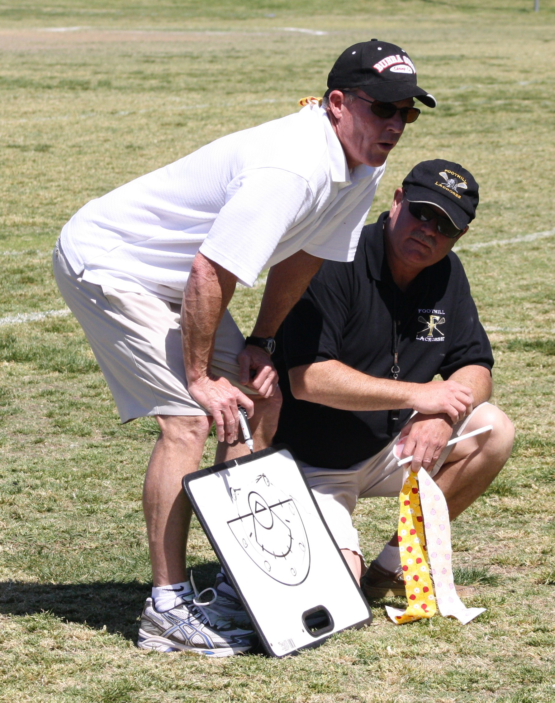 Foothill Varsity Girls Lacrosse Head Coach Brian Cross (right) and Coach Chris Cummins discuss strategy before game with Cate School.