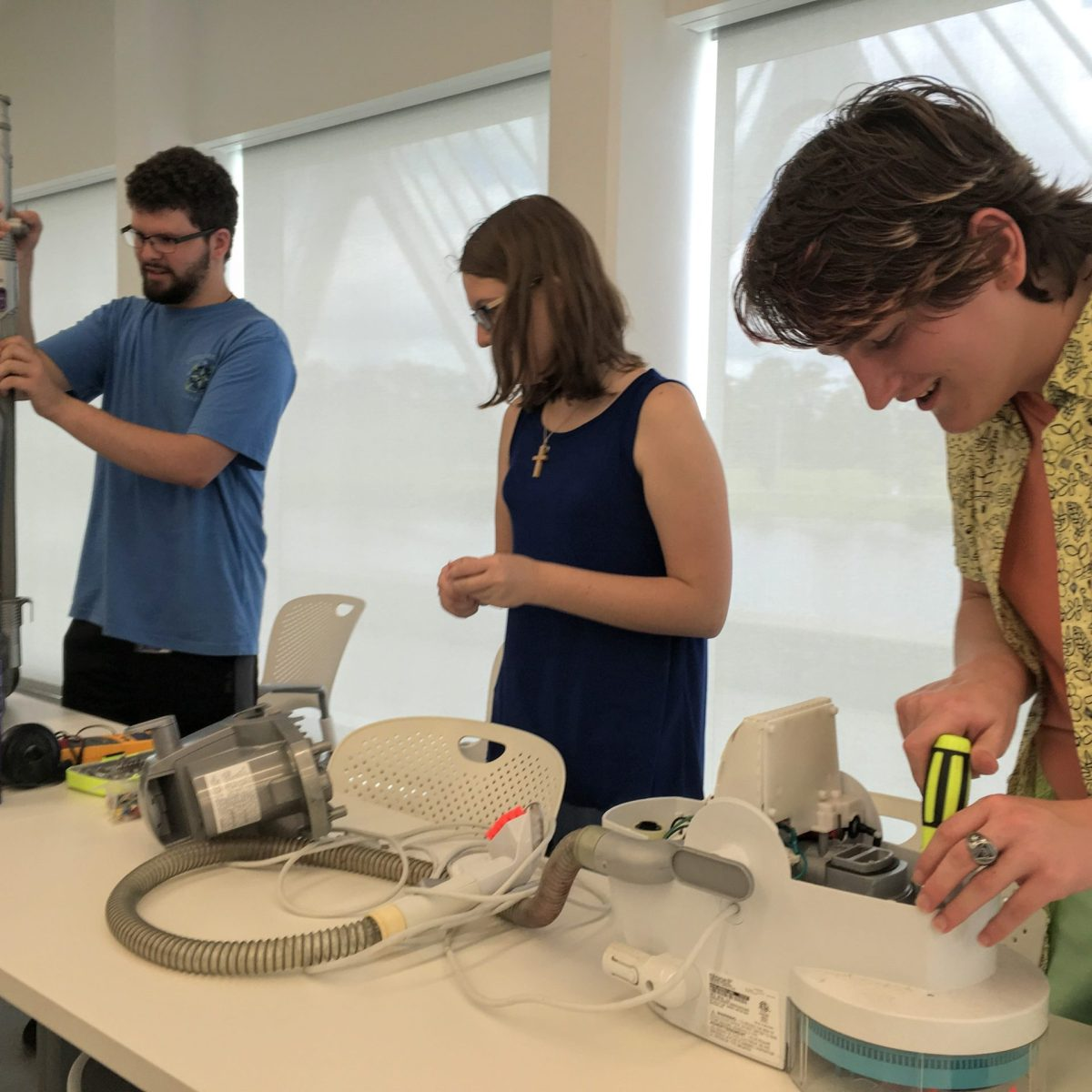 Students disassembling a vacuum cleaner at Purple Fire Hacks