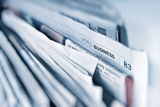 """Journaux papier quotidiens droit, un coin dépasse on voit """"business"""""""