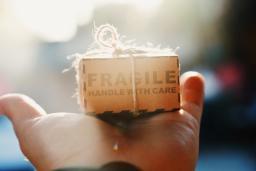 """boîte """"fragile"""" posée sur une main"""