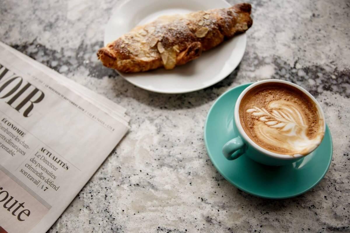 Café, croissant aux amandes, et journal