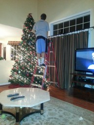 The tree is almost completed as my brother, Parker, places the angel on the top of the tree.