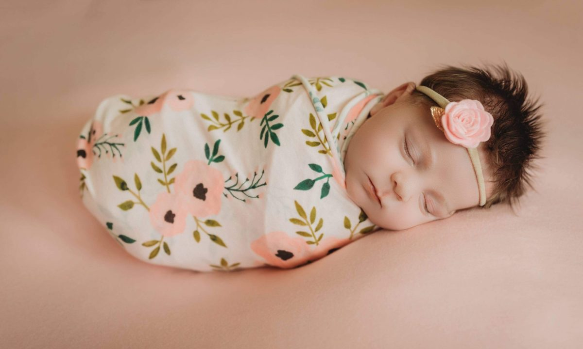in newborn photography session with baby girl newborn posed on bed