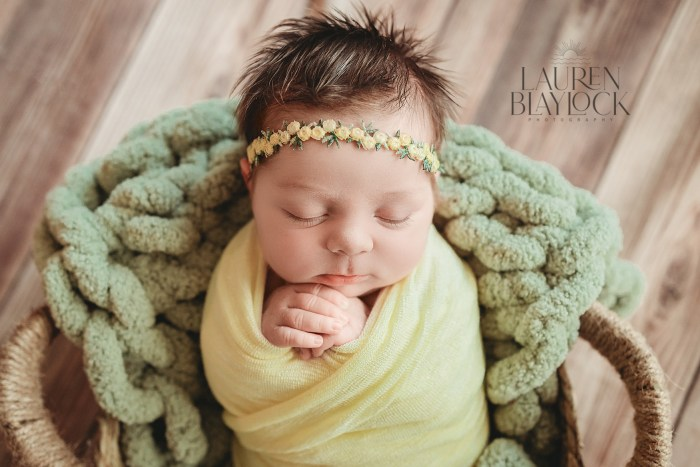 Newborn baby girl poses for Newborn Photographer Tampa. Author is discussing an why a custom newborn photography session is better than hospital newborn photos.