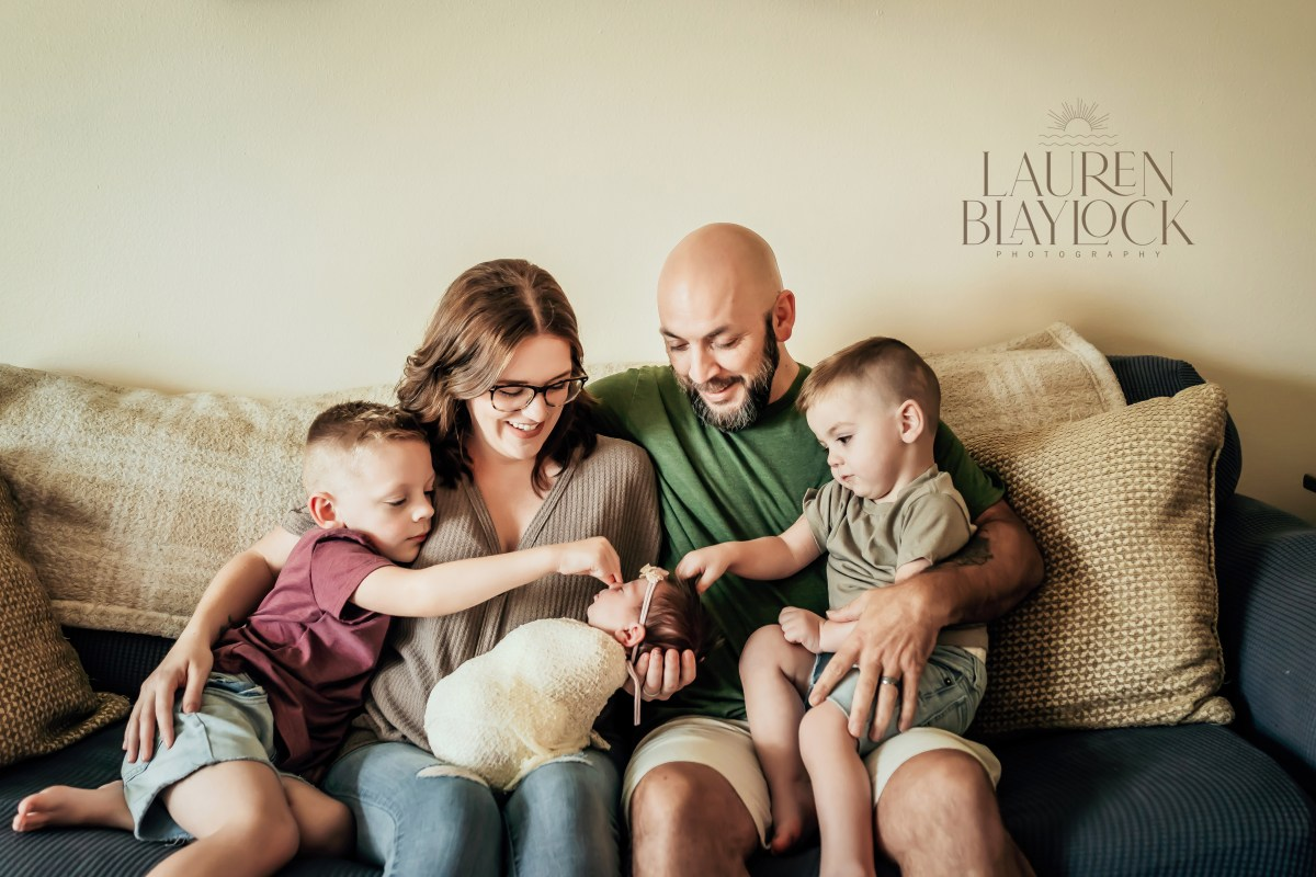 Family smiling at their newborn baby girl during tampa newborn photography session