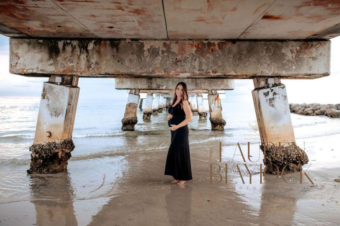 pregnant woman posing under fort desoto bridge during beach maternity photo session
