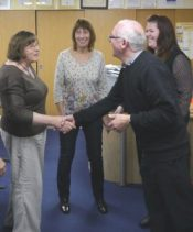 Two people shaking hands while others watch for assertiveness training