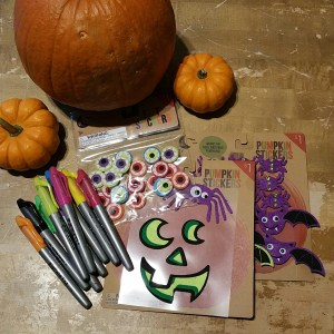 `The decorating supplies: pumpkins + stickers + markers