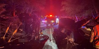 The wreckage of two vehicles was splayed across Highway 101 in south Depoe Bay Wednesday night after a Ford F350 (left) drifted across the center line and collided head-on with a Kia Spectra, leaving one driver dead and another critically injured and under investigation. (Photo by Depoe Bay Fire District)