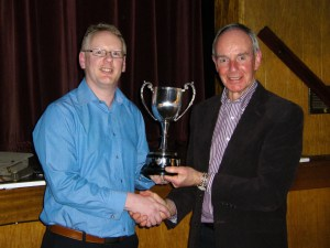 Chorley President Will Stead receiving the trophy from judge Richard Spiers