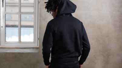 trendy young african american man in total black outfit standing near window