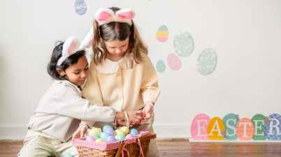 cute diverse girls playing with colorful easter eggs