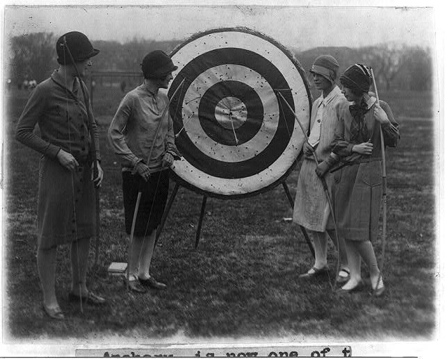 4 girls of Marjorie Webster school examining archery target - Louise Walraven, Imogene Koonce, Helyn Braskie and Helen Ackerman