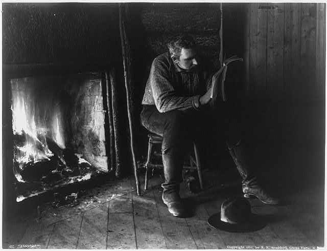 [Adirondack Mountains, N.Y.: Absorbed - man reading by fireplace]