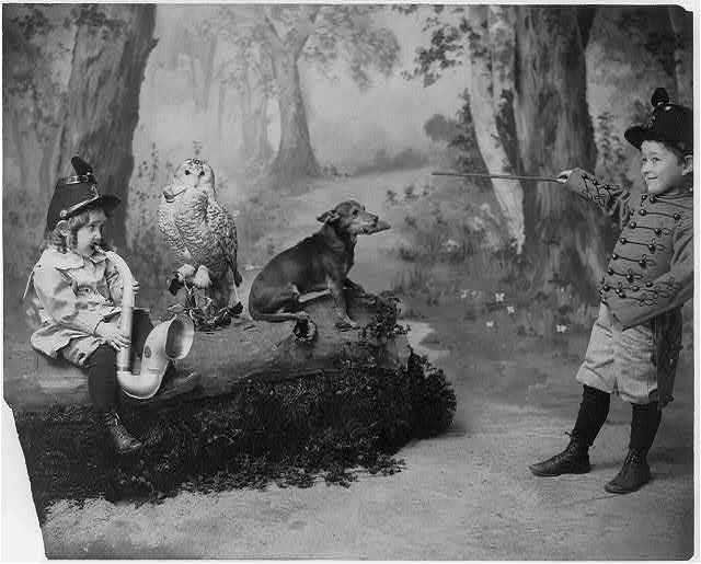[Girl playing horn, owl smoking pipe, boy in uniform conducting dog playing harmonica]