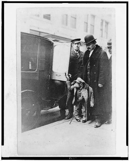 [Chimpanzee in clothing at door of automobile, with three men, at Napoleon Hippodrome]