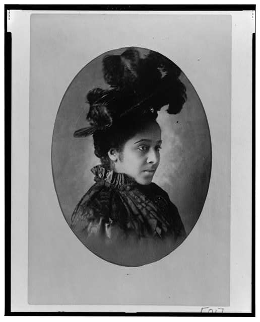 [African American woman, head-and-shoulders portrait, wearing hat, facing right]