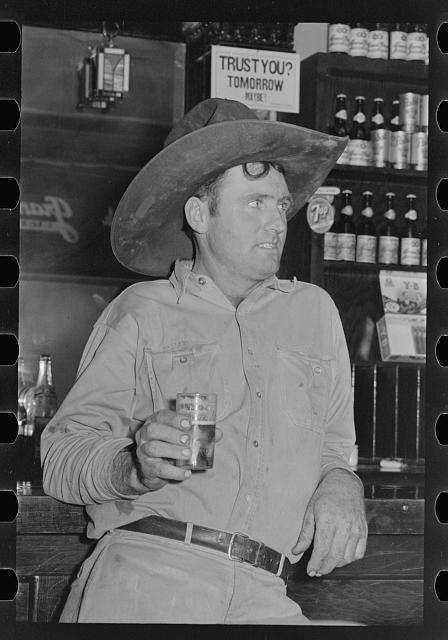 Cowboy drinking beer in beer parlor, Alpine, Texas