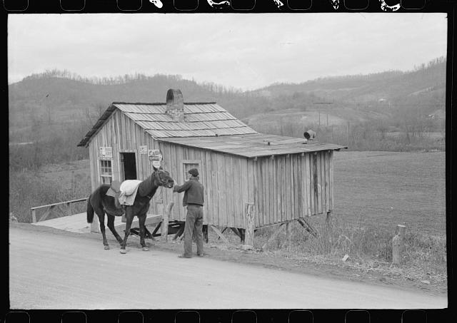 Mule carrying sack of meal in front of country store, Knox County, Kentucky