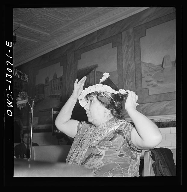 New York, New York. Gypsy woman putting on a paper cap on New Years' Eve in an Italian restaurant on Mulberry Street
