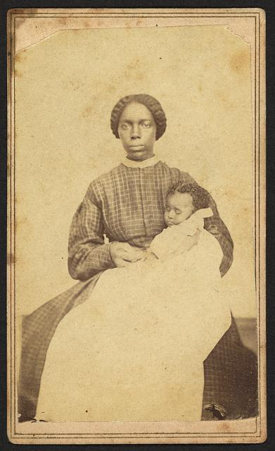 [Full-length portrait of an African American woman seated holding an African American infant]
