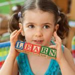 "Little girl holding up toy blocks that spell ""LEARN""."