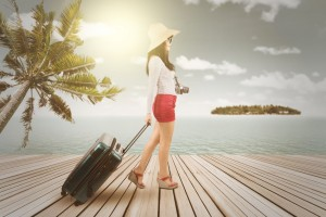 Female traveler walking on the pier while carrying a suitcase, shot with an instagram filter