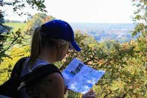 Femme regardant une carte devant un paysage