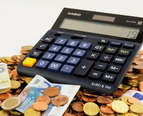 Taschenrechner auf Haufen Münzen