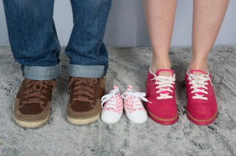 New Parents With Shoes And Baby Shoes Next To Them.
