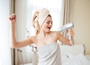 Funny woman singing in hairdryer at home