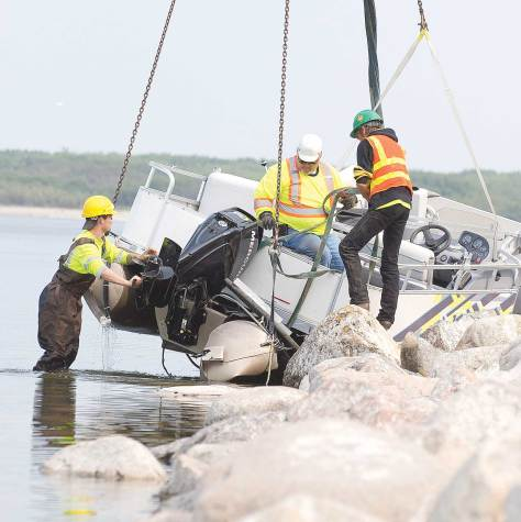Mark Janke and Chris and Keith Bryenton of Coppertop Towing in Elbow secure tow straps under a pontoon boat they were tasked with recovering from the rocks of the Qu'Appelle dam at Lake Diefenbaker.