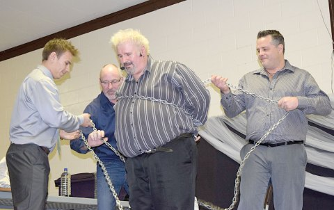Comedian-magician Perry James (centre) is bound in chains during his performance at the Davidson swimming pool committee's winter gala on Dec. 3. Helping him out, from left, are Terence Shewchuk, Derrick Vetter and Jason Low.