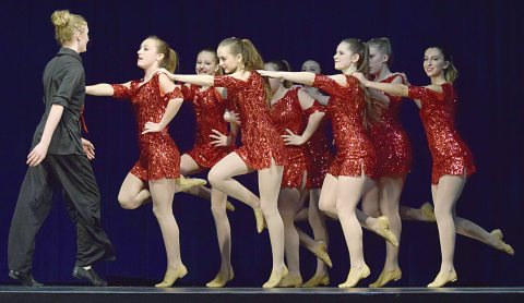 "Avery Ebenal faces a team of dancers — from left, Macy Palmer, Brooklyn Ruehlen, Jesselynne Palmer, Hannah Gust, Meghan Allan, Mackenzie Beck, Brookelynn Wick and Bella Thomson — in the opening jazz dance, ""Enough."""