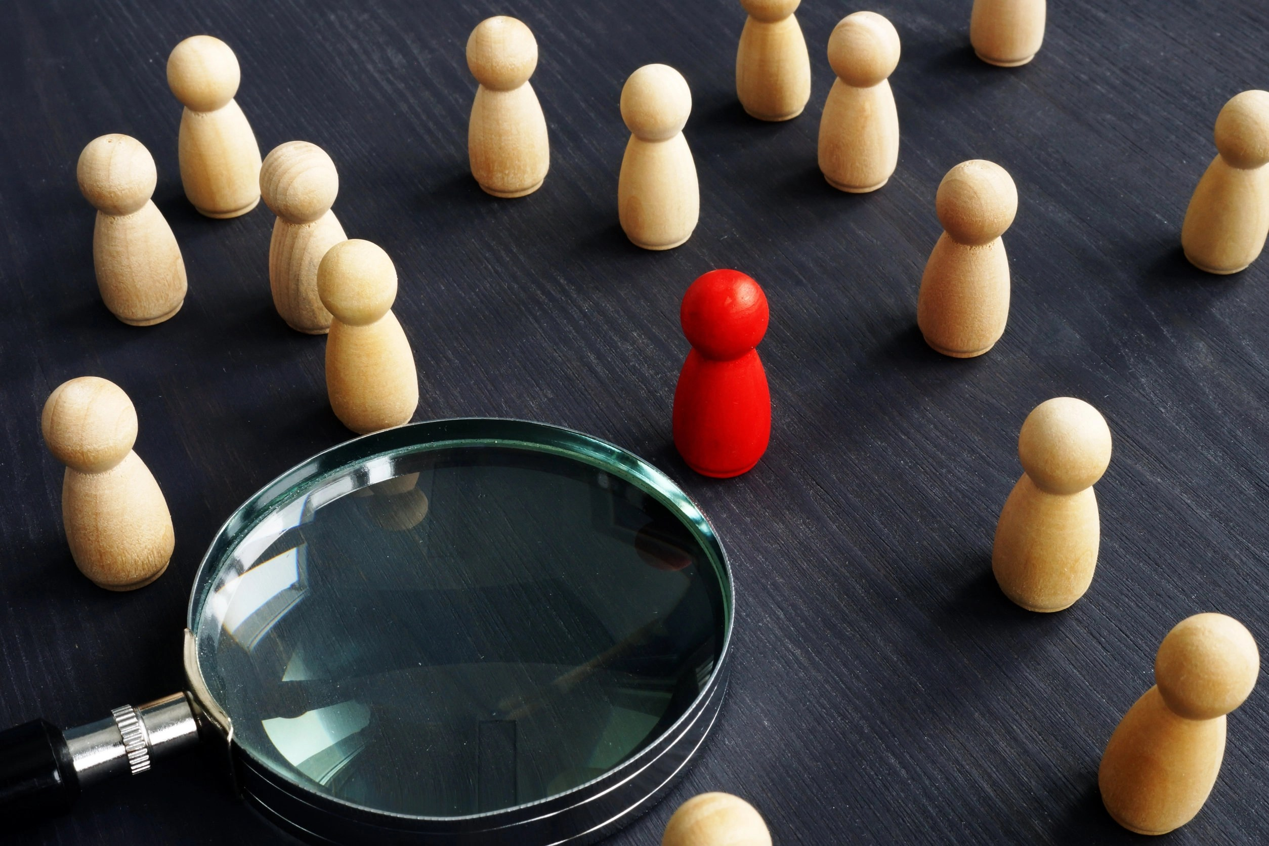 Wooden figures and magnifying glass. Personnel selection concept. Hiring people to work.